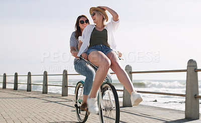 Buy stock photo Full length shot of a happy young couple riding a bicycle together on a promenade near the beach