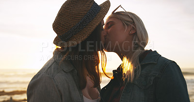 Buy stock photo Shot of an affectionate and happy young couple kissing while spending the day together outdoors near the beach