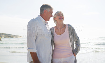 Buy stock photo Cropped shot of an affectionate senior couple having a laugh together at the beach on a summer's day