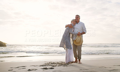 Buy stock photo Full length shot of an affectionate senior couple embracing each other at the beach during the day
