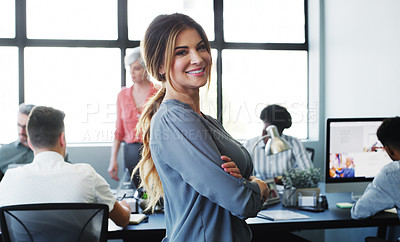 Buy stock photo Portrait of a confident young businesswoman working in a modern office with her colleagues in the background