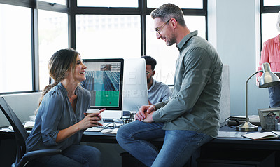 Buy stock photo Shot of a businessman and businesswoman having a discussion and using a computer together in a modern office