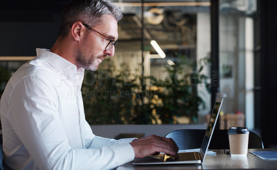 Buy stock photo Shot of a mature businessman using a laptop in a modern office