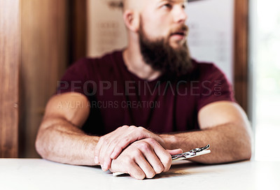 Buy stock photo Cropped shot of a barber holding a pair of scissors inside his barbershop