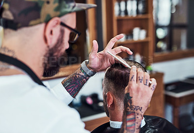 Buy stock photo Cropped shot of a handsome young barber giving a client a haircut inside his barbershop