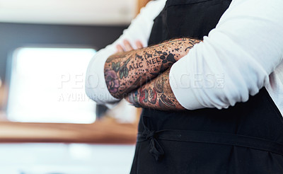 Buy stock photo Cropped shot of an unrecognizable tattooed barber posing with his arms folded inside a barbershop