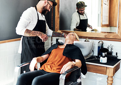 Buy stock photo Cropped shot of an attractive young woman getting her hair washed and styled by a hairdresser inside a salon
