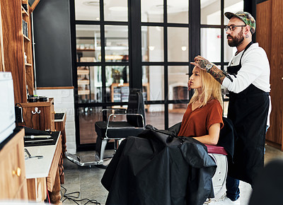 Buy stock photo Full length shot of an attractive young woman getting her hair styled and treated by a hairdresser at a salon