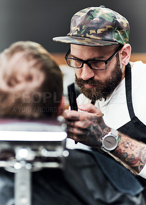 Buy stock photo Cropped shot of a handsome young barber trimming and lining up a clients beard inside a barbershop