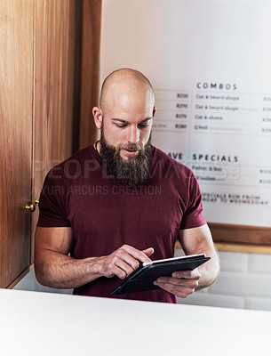 Buy stock photo Cropped shot of a handsome young barber using a digital tablet while working inside his barbershop