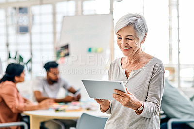 Buy stock photo Cropped shot of a senior businesswoman standing and using a tablet in the office while her coworkers sit behind her