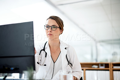 Buy stock photo Cropped shot of an attractive young female doctor working on a computer in her office at the hospital