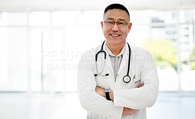 Buy stock photo Portrait of a mature doctor posing with his arms folded inside a hospital