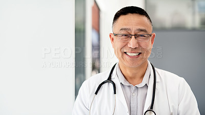 Buy stock photo Portrait of a mature male doctor feeling cheerful and confident while working inside a hospital
