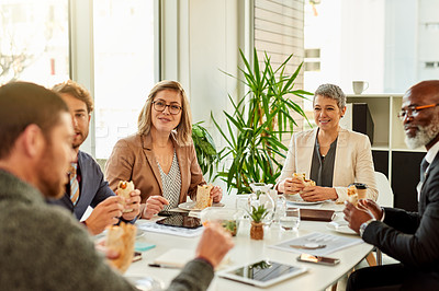 Buy stock photo Cropped shot of businesspeople having lunch while having a meeting in the boardroom