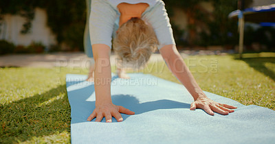 Buy stock photo Cropped shot of an unrecognizable senior woman holding a downward facing dog pose while doing yoga in her back garden