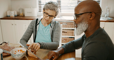 Buy stock photo Cropped shot of a senior couple sitting together and using a tablet in their kitchen before breakfast