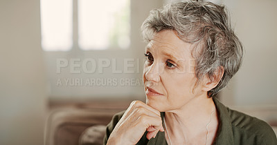 Buy stock photo Cropped shot of a senior woman sitting alone on the sofa and looking contemplative during a day home