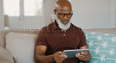 Buy stock photo Cropped shot of a happy senior man sitting alone on his sofa and using a tablet during a day home