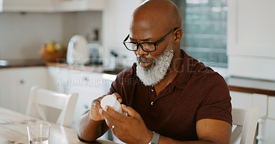 Buy stock photo Cropped shot of a senior man sitting alone in his kitchen and taking pills