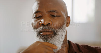 Buy stock photo Cropped shot of a senior man sitting alone on the sofa and looking contemplative during a day home