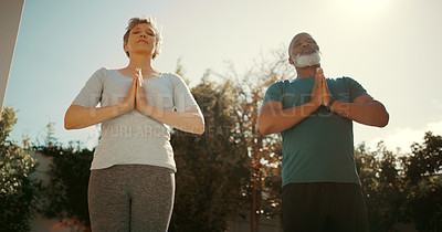 Buy stock photo Low angle shot of a senior couple standing together and meditating together in their garden