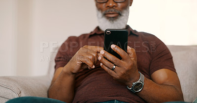 Buy stock photo Cropped shot of an unrecognizable man sitting on his sofa and using his cellphone during a day off at home