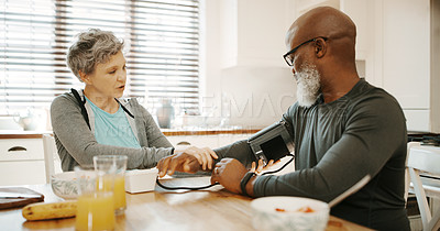 Buy stock photo Cropped shot of an affectionate senior woman sitting and checking her husband's blood pressure in their kitchen