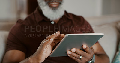 Buy stock photo Cropped shot of an unrecognizable man sitting alone on his sofa and using a tablet during a day home