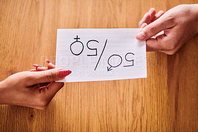 Buy stock photo Cropped shot of an unrecognizable man and woman holding a piece of paper promoting gender equality over a wooden table