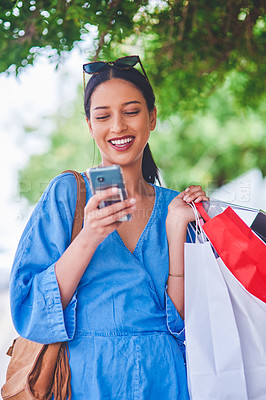 Buy stock photo Cropped shot of an attractive young woman using a smartphone while holding shopping bags in the city during the day