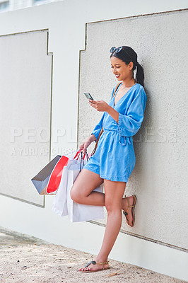 Buy stock photo Full length shot of an attractive young woman using a smartphone while holding shopping bags in the city during the day