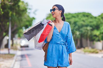 Buy stock photo Cropped shot of an attractive young woman smiling while holding shopping bags in the city during the day
