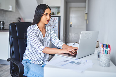 Buy stock photo Cropped shot of an attractive young businesswoman sitting alone and using her laptop while at  home