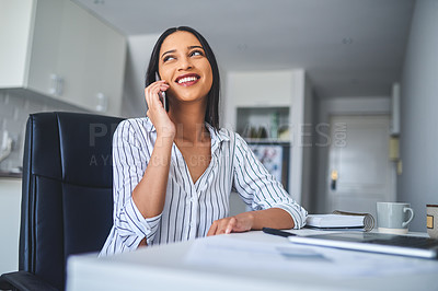 Buy stock photo Cropped shot of an attractive young businesswoman sitting alone and talking on her cellphone while at home