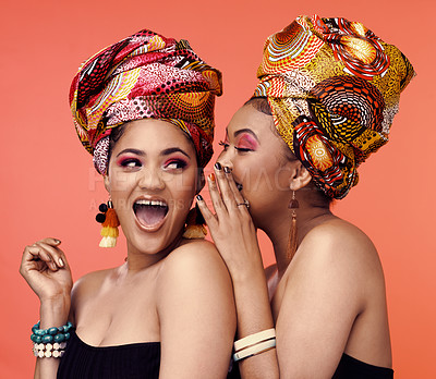 Buy stock photo Studio shot of two attractive young women wearing traditional  African head wraps posing together against an orange background