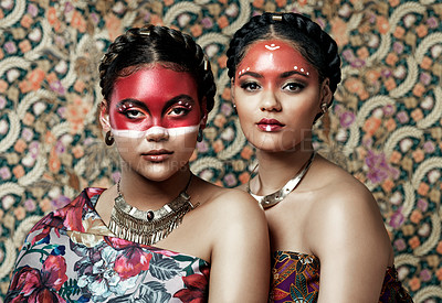 Buy stock photo Portrait of two attractive young women dressed in traditional attire and makeup posing together against a patterned background