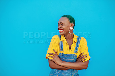 Buy stock photo Shot of a beautiful young woman posing against a blue wall