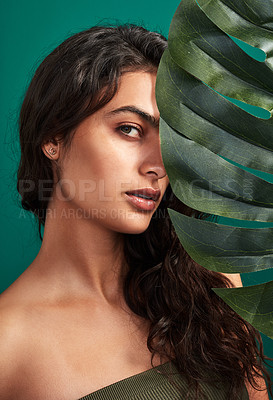 Buy stock photo Cropped shot of a beautiful young woman posing with a monstera leaf against a green background