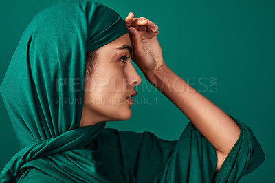Buy stock photo Cropped shot of a beautiful young woman wearing a headscarf against a green background