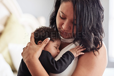 Buy stock photo Cropped shot of an affectionate young single mother holding her sleeping baby at home