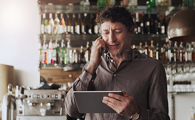 Buy stock photo Shot of a cafe owner talking on his cellphone while using a digital tablet
