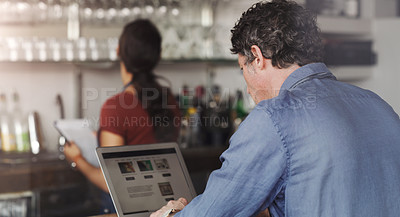 Buy stock photo Shot of a customer using his laptop in a coffee shop