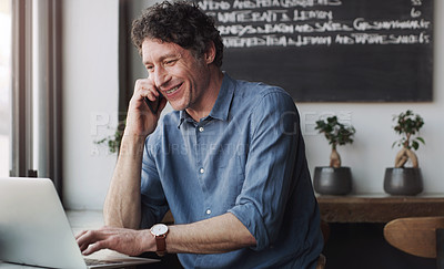 Buy stock photo Shot of a customer talking on his cellphone while using his laptop in a coffee shop