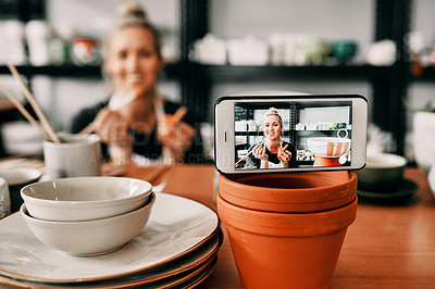 Buy stock photo Cropped shot of an attractive mature woman using her cellphone to record her pottery process for her blog