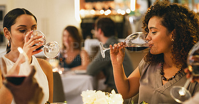 Buy stock photo Cropped shot of a group of cheerful young friends having wine while dining together in a restaurant