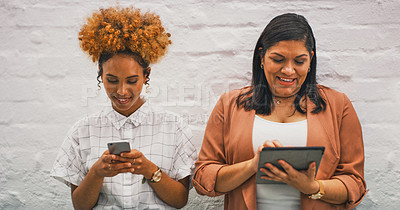 Buy stock photo Shot of  two businesswomen using their wireless devices in a modern office