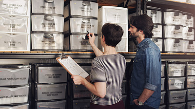 Buy stock photo Shot of a businessman and businesswoman doing inventory in a storage room