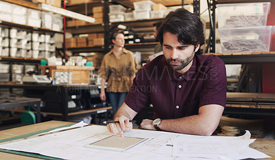 Buy stock photo Shot of a young businessman using a digital tablet while designing a blueprint in a creative office