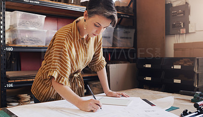 Buy stock photo Shot of a businesswoman designing a blueprint in a creative office